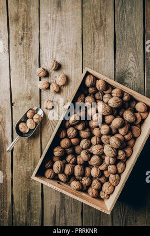 top view of tasty healthy walnuts in box on wooden table - Stock Photo