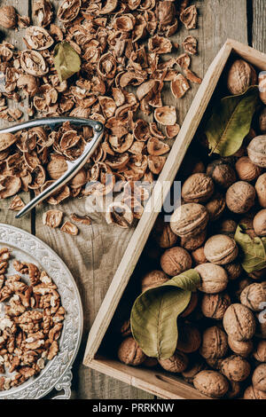 top view of walnuts in box, nutcracker and nutshells on wooden table - Stock Photo