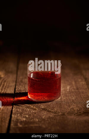 close up view of tasty mulled wine in glass on wooden surface - Stock Photo