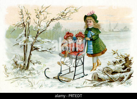 Young woman slides sledge with two little girls and doll, - Stock Photo