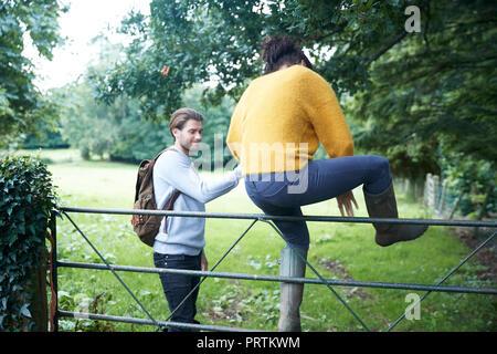 Hiker couple climbing over farm gate - Stock Photo