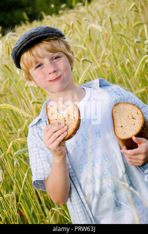boy with bread in a wheat field - Stock Photo