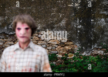 an intentionally unfocused scary disfigured man, wearing dirty and ragged clothes, in front of a ruined and abandonded house, the point where the focu - Stock Photo