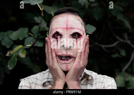 closeup of a scary disfigured man, wearing dirty and ragged clothes, with his hands in his face, in the woods - Stock Photo