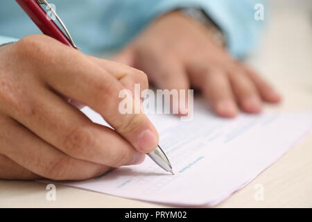 Man is filling form with pen. - Stock Photo