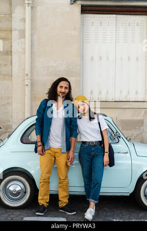 Portrait of young couple standing at small car - Stock Photo