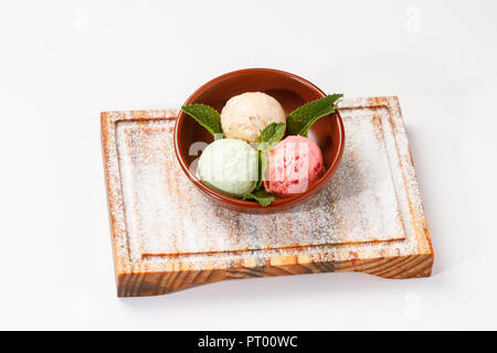 Ice cream with Mint leaves served in a bowl on top of a wooden board on white Background. 3 scoops; Raspberry, pistachio and Caramel - Stock Photo
