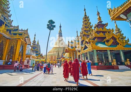 YANGON, MYANMAR - FEBRUARY 27, 2018: The group of bhikkhu monks visits Shwedagon Zedi Daw, walking along the beautiful shrines to the main stupa, on F - Stock Photo