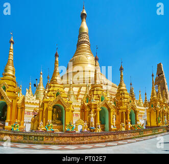 The huge main stupa of Shwedagon Zedi Daw is towering behind the hundreds of small outer stupas, decorated with ringing hti umbrellas and Buddha image - Stock Photo
