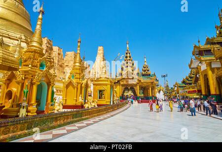 YANGON, MYANMAR - FEBRUARY 27, 2018: The stupas of Shwedagon Pagoda complex with main Eastern Shrine - Kakusandha Buddha Image House on the distance,  - Stock Photo
