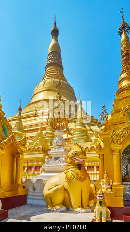The large statue of chinthe (leogryph) among the outer stupas of Shwedagon with its main pagoda on background, Yangon, Myanmar. - Stock Photo