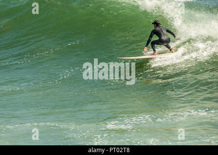 Surfer riding a large point break wave at Sunset Point in Pacific Palisades, Los Angeles County, California. (USA) - Stock Photo