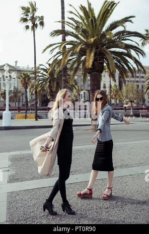 Spain, Barcelona, two fashionable young women on the street - Stock Photo