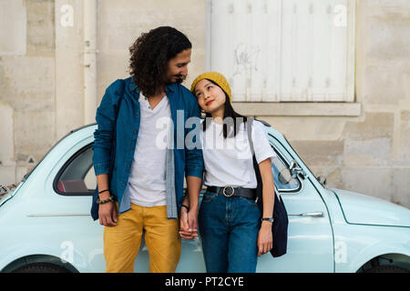 Young couple in love standing at small car - Stock Photo
