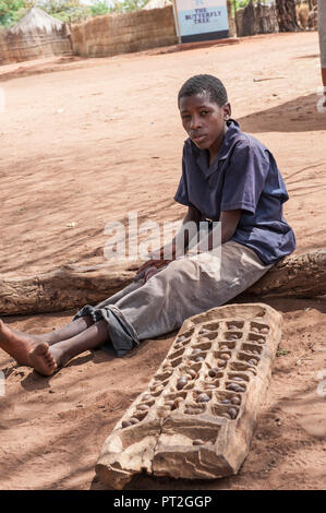 A local boy from Mukuni Village with a hand carved game called Nsolo or Mancala that is popular in Zambia, based on a game called dodge ball. - Stock Photo
