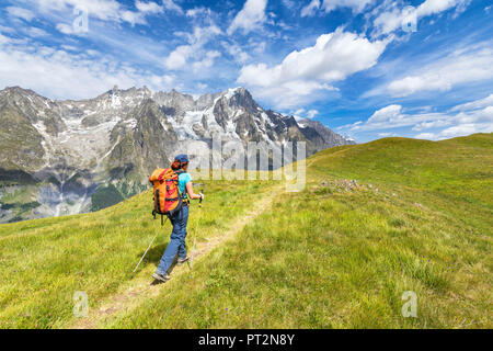 A trekker is walking on the Mont de la Saxe in front of Grandes Jorasses during during the Mont Blanc hiking tours (Ferret Valley, Courmayeur, Aosta province, Aosta Valley, Italy, Europe) - Stock Photo