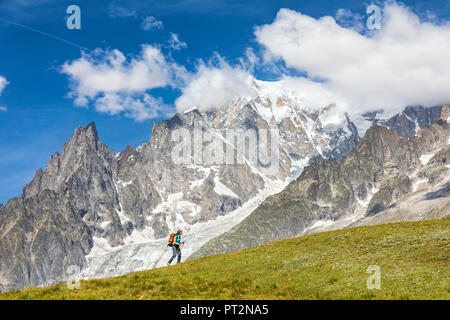 A trekker is walking in front of the Mont Blanc during the Mont Blanc hiking tours (Ferret Valley, Courmayeur, Aosta province, Aosta Valley, Italy, Europe) - Stock Photo