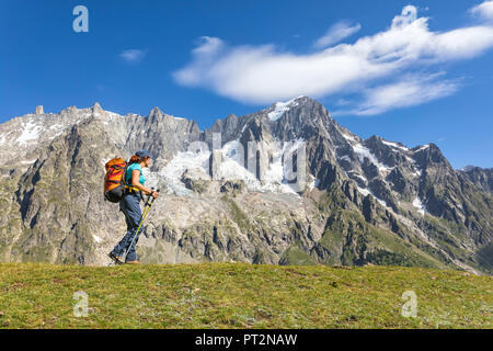 A trekker is walking in front of the Grandes Jorasses during the Mont Blanc hiking tours (Ferret Valley, Courmayeur, Aosta province, Aosta Valley, Italy, Europe) - Stock Photo