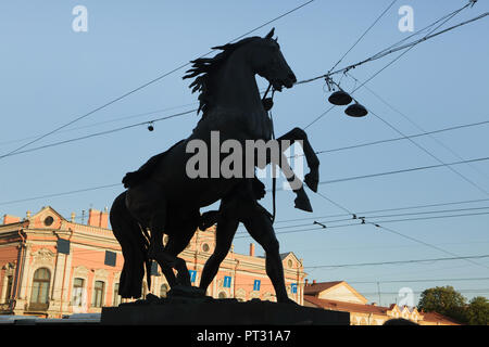 Horse Tamers by Russian sculptor Peter Clodt von Jürgensburg (Pyotr Klodt) on the Anichkov Bridge across the Fontanka River in Saint Petersburg, Russia, pictured silhouetted at sunset. - Stock Photo