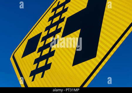 Abstract Railroad crossing sign at angle with blue sky - Stock Photo