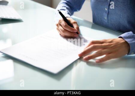 Businesswoman's Hand Signing Contract With Pen Over Desk - Stock Photo
