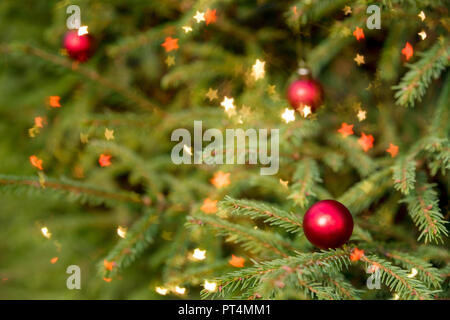 Decorated Christmas tree on blurred, sparkling and fairy background.Magically decorated Christmas Tree with red balls, on a blurred shiny, sparkling background. Happy new year card - Stock Photo