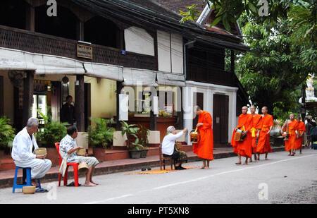 Monks accepting alms, Luang Prabang - Stock Photo