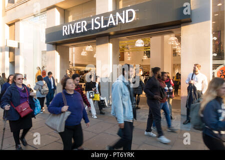 Pedestrians walking past the River Island Store, Oxford Street, London, UK, Europe, - Stock Photo