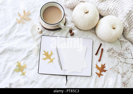 Autumn breakfast in bed composition. Blank cards, notebook mockup. Cup of coffee, white pumpkins, sweater, oak leaves and gypsophila flowers on linen background. Thanksgiving, Halloween. Flat lay. Top - Stock Photo