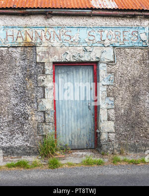 HEADFORD, IRELAND - AUGUST 8, 2018: The abandoned Hannon's Stores building next to a country road near Headford, in County Galway, Ireland. - Stock Photo