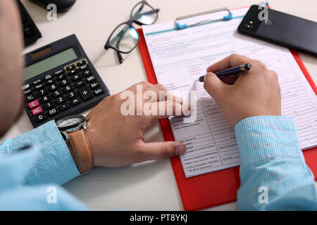 Man is filling form with pen. Picture of clipboard, phone, glasses, pen, form and calculator. - Stock Photo