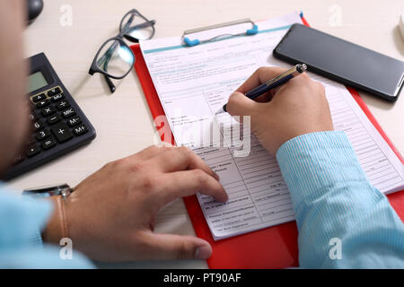 Man is filling form with pen. Portrait of clipboard, phone, glasses and calculator. - Stock Photo