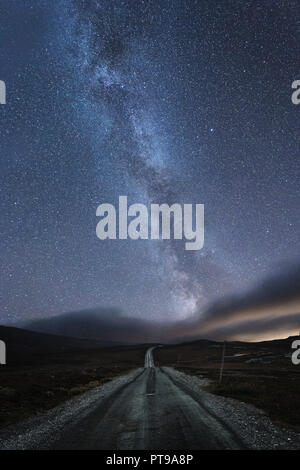 The road under starry sky with visible  Milky Way. Night in norwegian mountain area near Tydal, Stugudalen. - Stock Photo