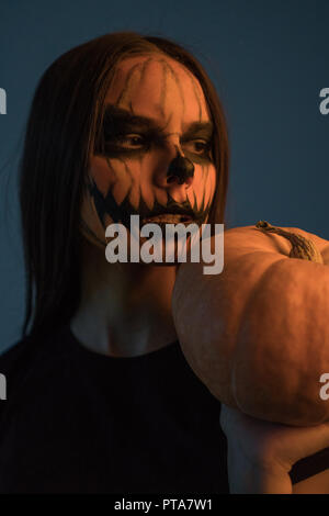 A girl in a dead man's mask with a pumpkin on a dark background. Halloween - Stock Photo