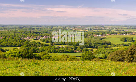 Sun shines on the village of Pett and a patchwork of woodland and farm fields in East Sussex as viewed from the high vantage point of Fairlight hill. - Stock Photo