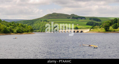 Row boats are moored in Ladybower Reservoir, in front of the A57 Snake Road bridge and Crook Hill in England's Peak District. - Stock Photo