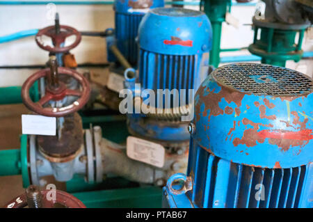 Old blue electric motor with pump, gate valve on the pipeline. Industrial background. - Stock Photo