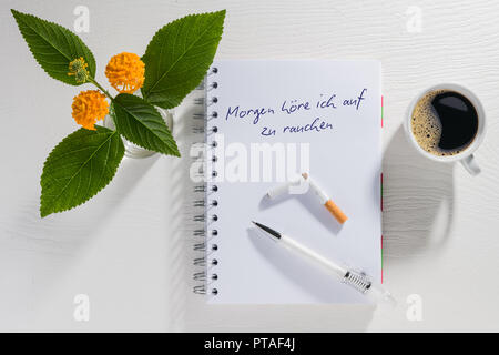 Writing pad with New Year's resolution with coffee cup and flowers on a white table - Stock Photo