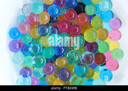 A colorful white bowl of full water beads. - Stock Photo