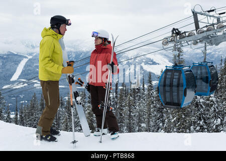 Senior couple interacting with each other in snowy landscape - Stock Photo