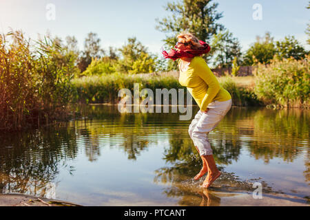 Middle-aged woman jumping on river bank on autumn day. Happy senior lady having fun walking in the forest - Stock Photo