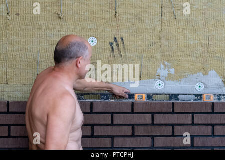 Bricklayer Using a Spirit Level to Check New Red Brick Wall Outdoor. - Stock Photo