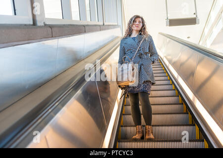 Low angle view, looking up of young woman standing on metro, subway, airport escalator going down with stairs, steps, bright light outside - Stock Photo