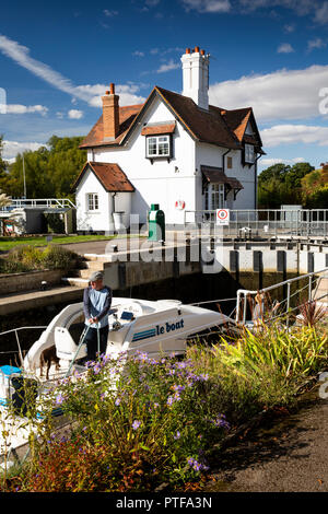 England, Berkshire, Goring on Thames, lock keepers cottage at locks on River Thames, as leisure boat passes through - Stock Photo