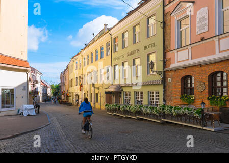 Vilnius old town, view on a summer morning of a young woman cycling along Pilies Gatve - the main thoroughfare in Vilnius Old Town, Lithuania. - Stock Photo