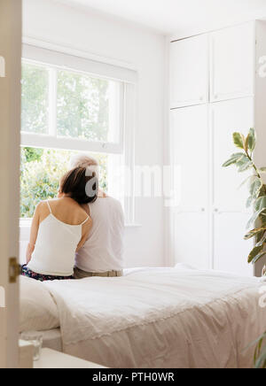 Serene senior couple sitting on bed and looking out window - Stock Photo