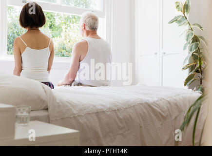 Thoughtful senior couple sitting on bed looking out window - Stock Photo