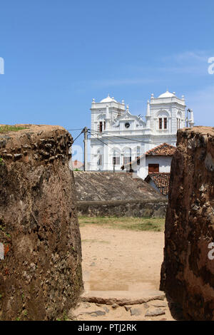 The Meera Mosqe within the Galle Fort, seen from between of two rocks. Taken in Sri Lanka, August 2018. - Stock Photo