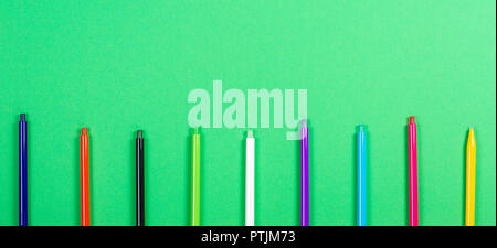 Set of colored pens on green background. - Stock Photo