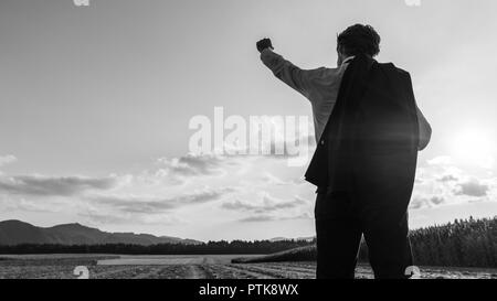 Businessman celebrating his success standing in evening nature with his jacket over his shoulder and one arm raised up high in celebration. - Stock Photo